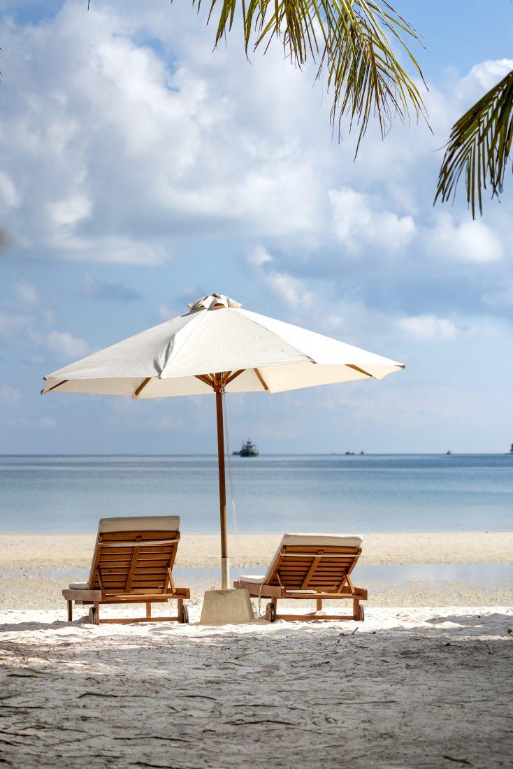 two-brown-wooden-armchairs-beside-umbrella-near-seashore-3355732